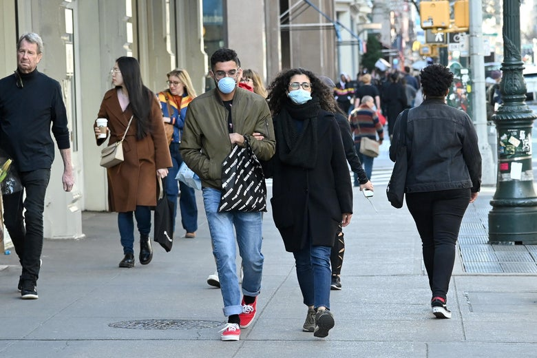 People wearing masks are seen as the coronavirus continues to spread across the United States on March 14, 2020 in New York City.