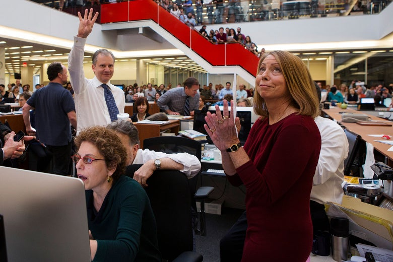 Staffers crowded in the New York Times newsroom as Pulitzer Prize winners are announced. Abramson looks up, clapping. Arthur Sulzberger Jr. holds up four fingers to signify four wins.