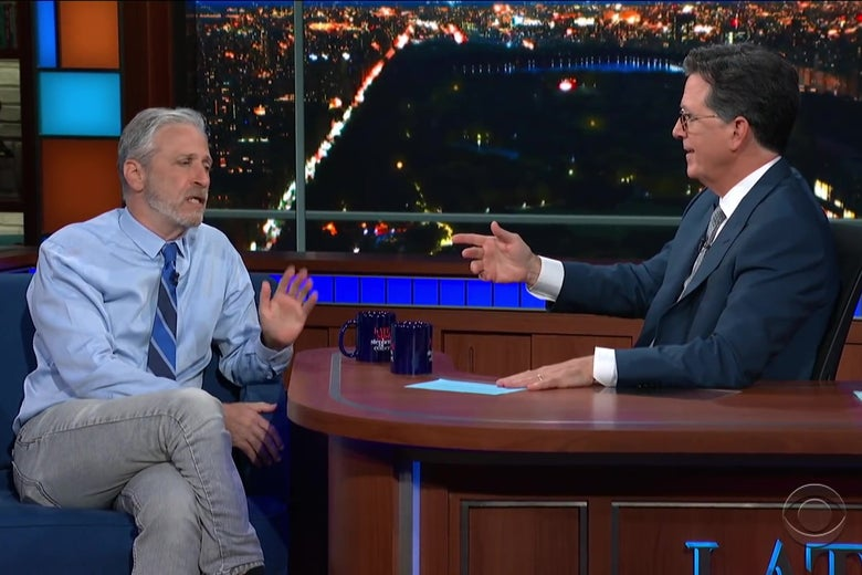 Jon Stewart, in a blue shirt, tie, and jeans, sits in the guest chair on the Late Show set, talking with Stephen Colbert, who sits behind the host's desk.