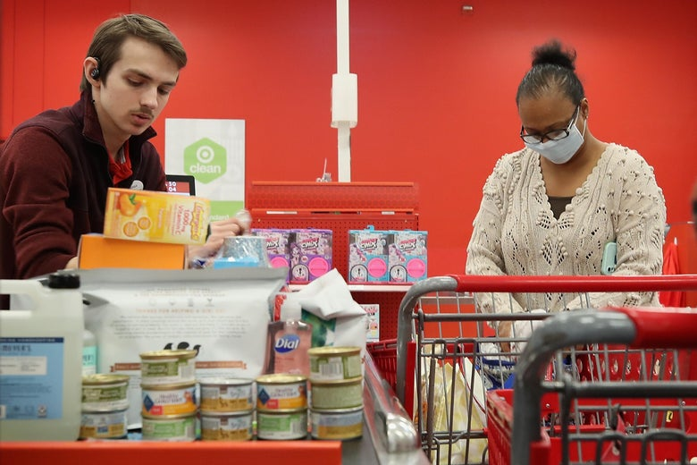 A shopper wearing a mask purchases grocery items at a Target store