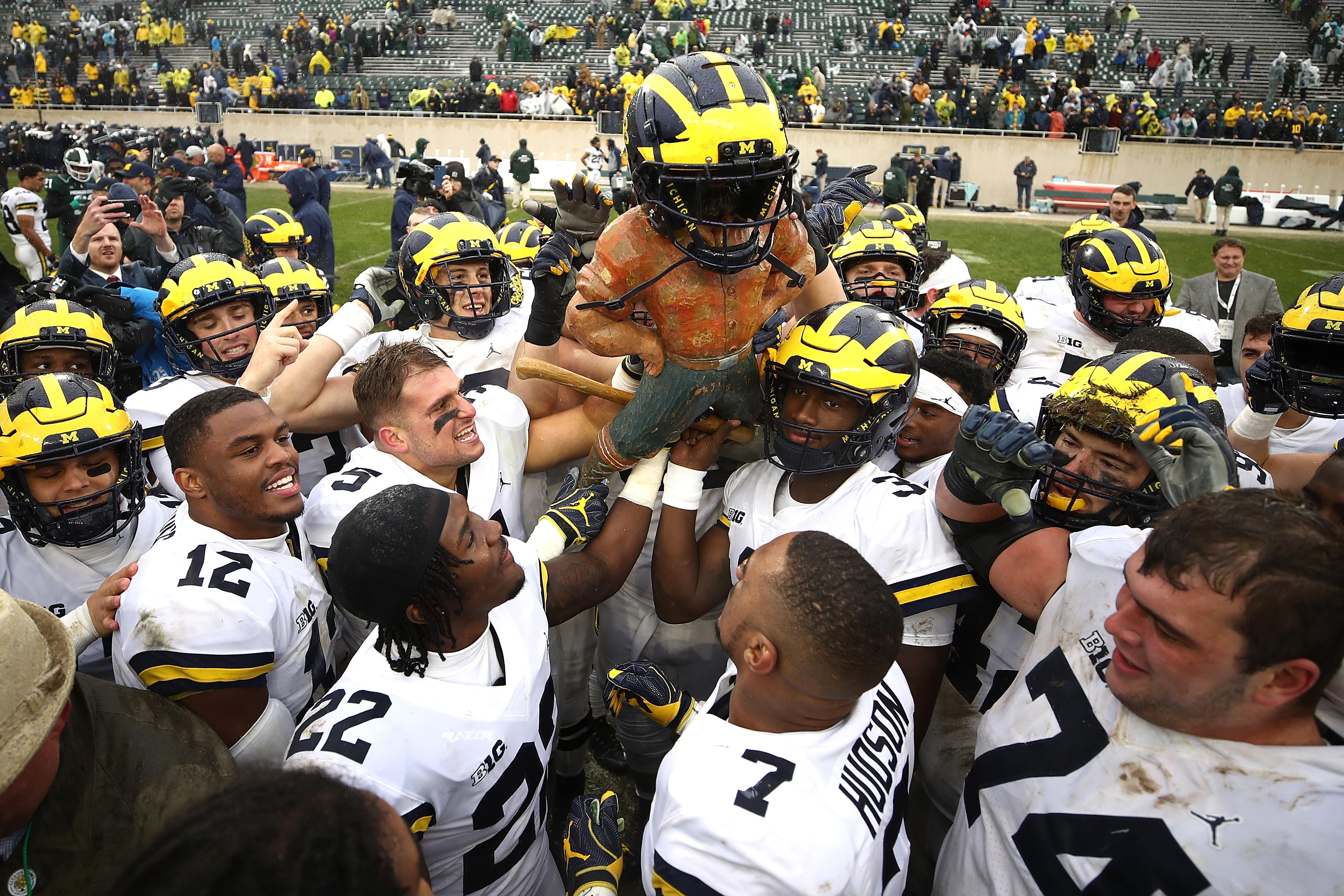 EAST LANSING, MI - OCTOBER 20:  The Michigan Wolverines celebrate winning the Paul Bunyan trophy with a 21-7 win over the Michigan State Spartans at Spartan Stadium on October 20, 2018 in East Lansing, Michigan. (Photo by Gregory Shamus/Getty Images)