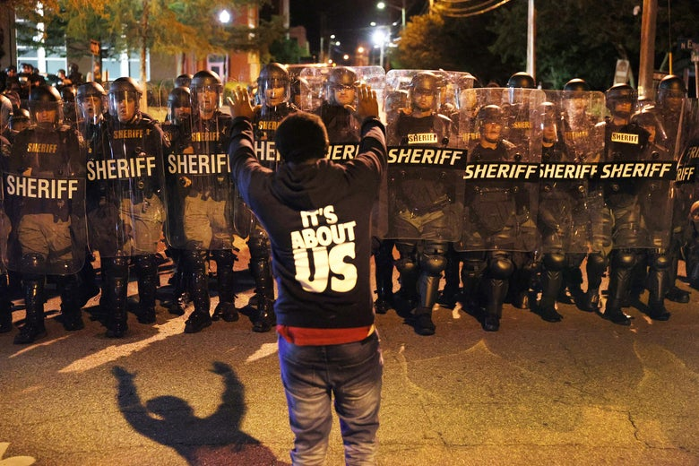 A protester stands with his arms raised in front of a line of law enforcement officials in riot gear.