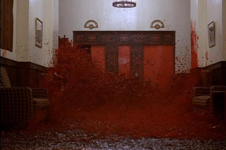 A wave of blood pours out of a hotel elevator in a still from The Shining.