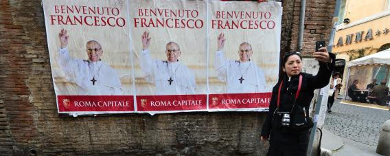 A woman poses in front of posters of Pope Francis on March 15, 2013, near St Peter's Square at the Vatican.