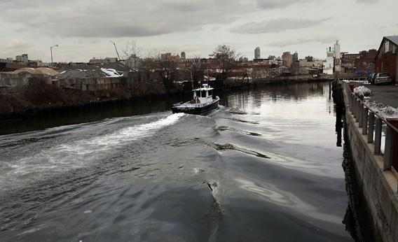 A boat navigates down the Gowanus Canal in Brooklyn, New York.