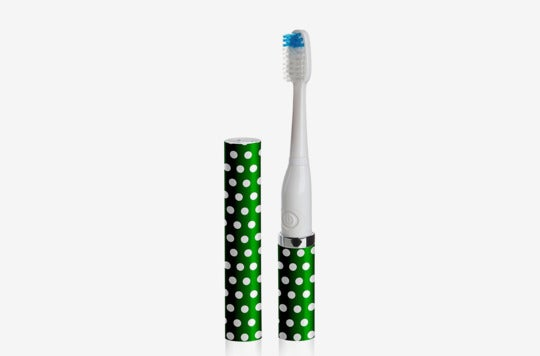 Green Violife toothbrush with white polka dots.