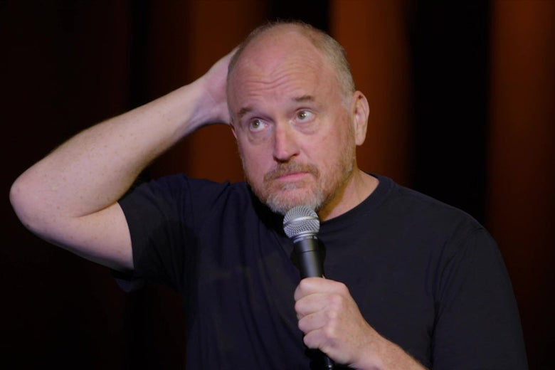 Comedian Louis C.K., wearing a blue T-shirt, holding a microphone on stage.
