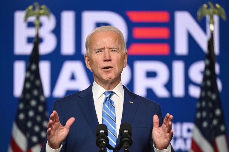 Joe Biden holds both hands up in front of him while speaking from behind a microphone.