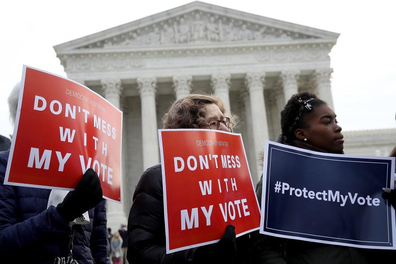 """Three protesters hold signs saying """"Don't Mess With My Vote"""" and """"#ProtectMyVote"""" on Wednesday in front of the Supreme Court building in Washington. Photo by Win McNamee/Getty Images."""
