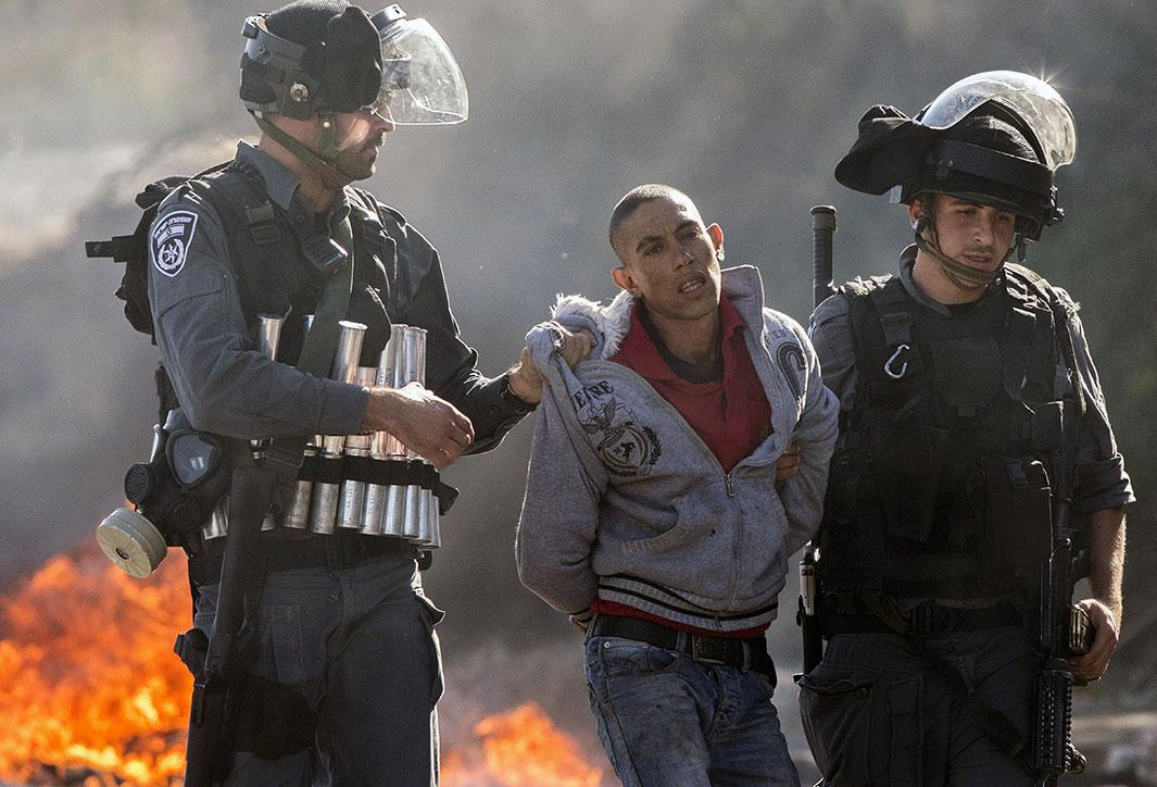 Israeli security forces detain an Arab-Israeli youth during clashes in the town of Kfar Kana, in northern Israel, on Nov. 9, 2014, a day after security forces shot dead a 22-year-old Arab-Israeli man. The dawn killing in Kfar Kana comes against a backdrop of soaring Israeli-Palestinian tensions in annexed east Jerusalem where there have been near-daily clashes in flashpoint neighborhoods. Arab-Israelis, who account for about 20 percent of Israel's population, are the descendants of Palestinian Arabs who remained on their land when the Jewish state was established in 1948