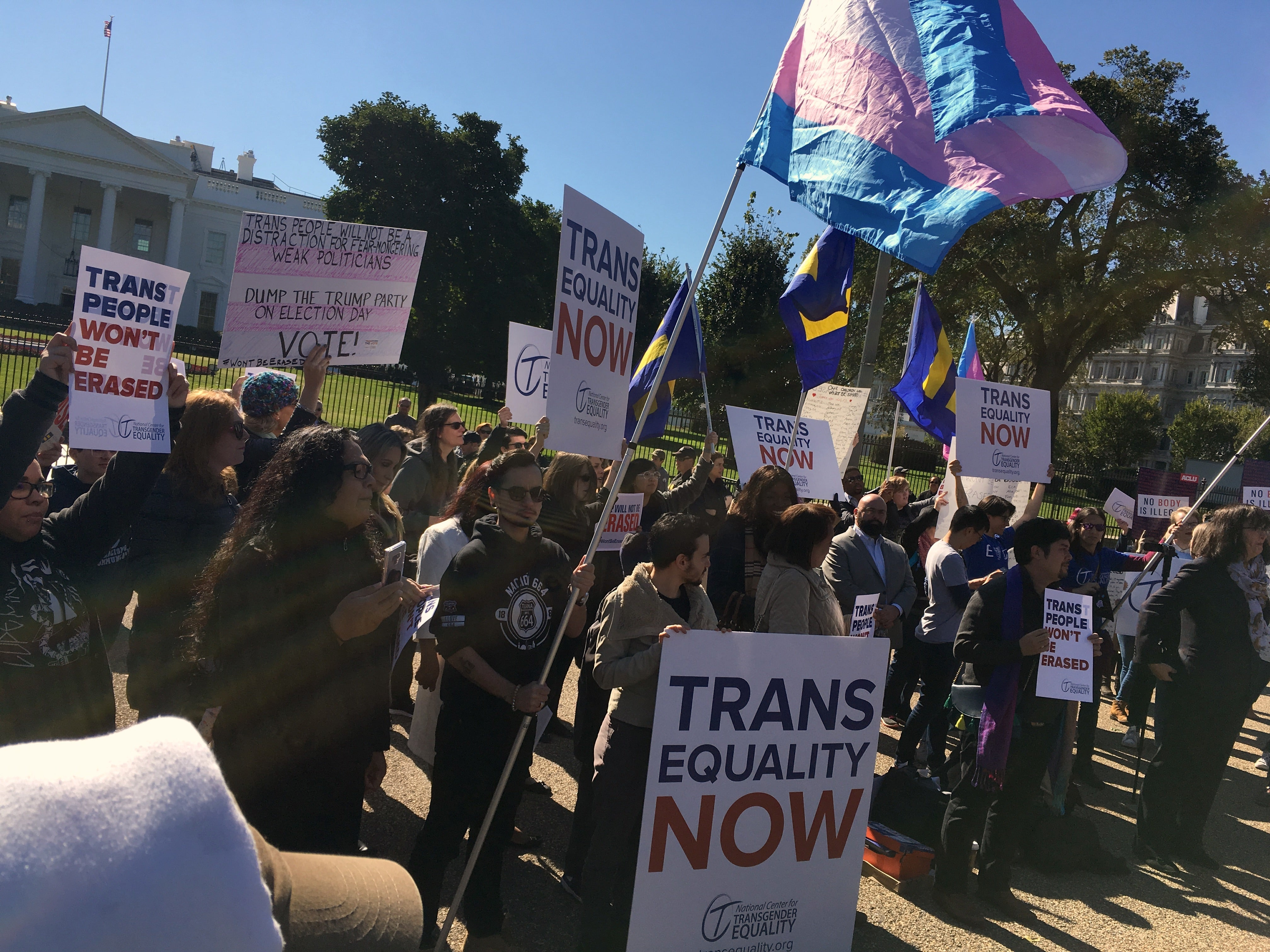 "Demonstrators holding signs that say ""Trans Equality Now"" and ""trans people won't be erased"" and waving a trans flag stand in front of the White House."