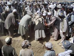 Afghan mourners prepare to bury victims during a funeral in Kunduz. Click image to expand.