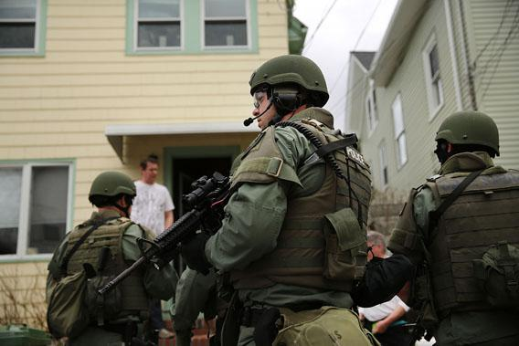Members of a police SWAT team conduct a door-to-door search for 19-year-old Boston Marathon bombing suspect Dzhokhar A. Tsarnaev on April 19, 2013 in Watertown, Mass.