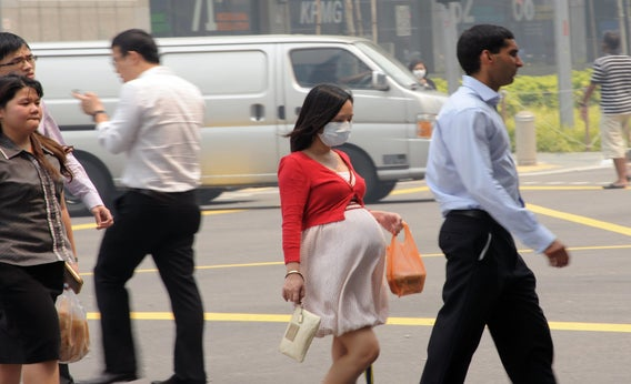 A pregnant woman with a face mask walking on the street in Singapore, June 20, 2013.