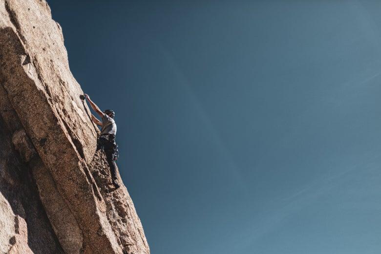 A man climbs a steep cliff.