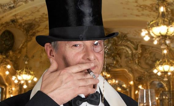Man in a tux wearing a monocle.