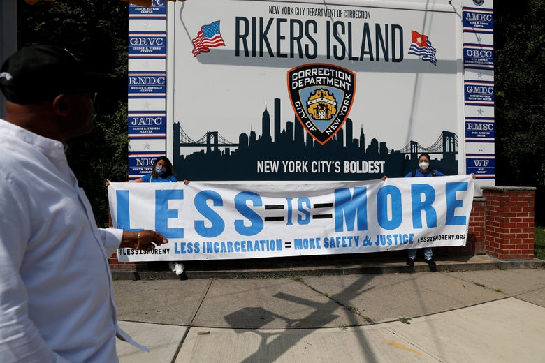 """Protests hold up a large banner that says, """"Less Is More"""" in front of the sign for Rikers Island."""