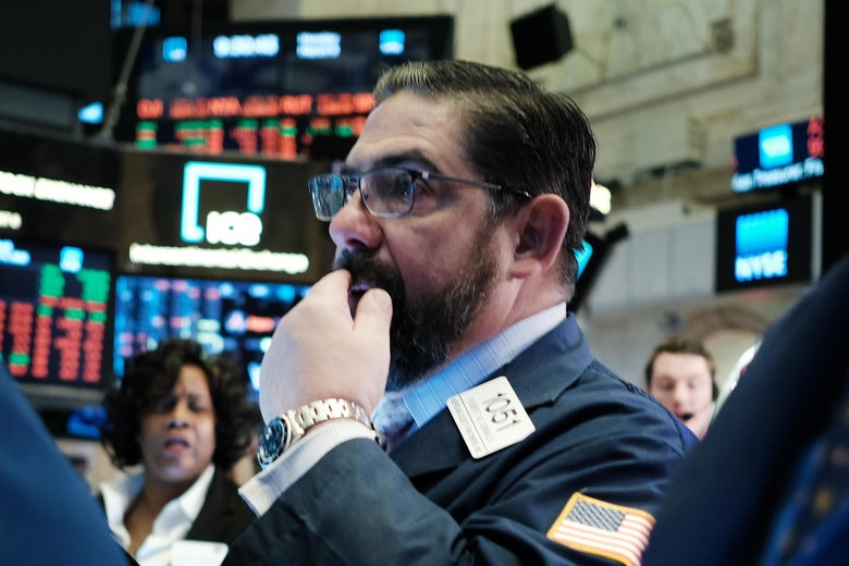 A trader on the floor of the New York Stock Exchange touches his face
