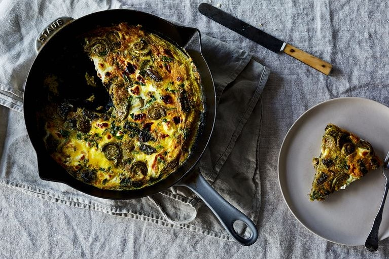 Overhead shot of cast iron pan containing a yellow fiddlehead fern frittata, with a slice carve out and sitting on a serving dish to the right of the pan.