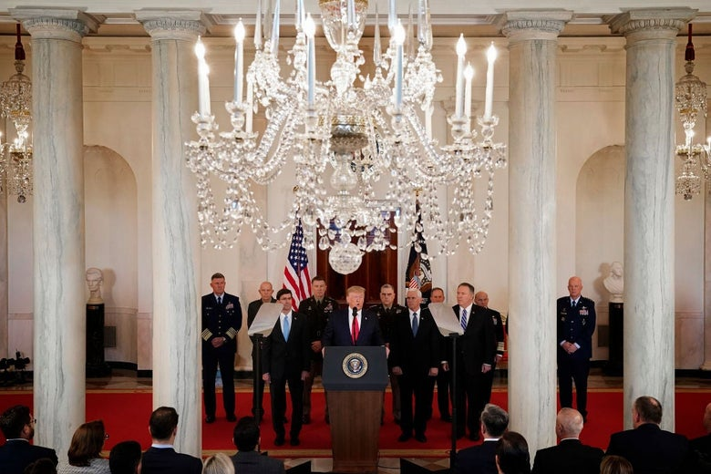 Trump is seen at the presidential lectern on a red carpet against a backdrop of white columns and a chandelier.
