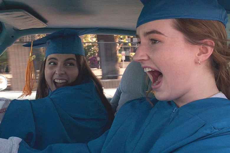 Beanie Feldstein and Kaitlyn Dever in a car wearing graduation caps and gowns Booksmart.
