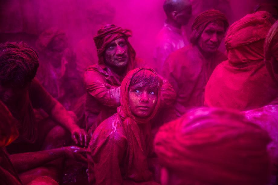 A boy looks on as Hindu devotees play with color during Lathmaar Holi celebrations on March 21, 2013 in the village of Barsana, near Mathura, India.