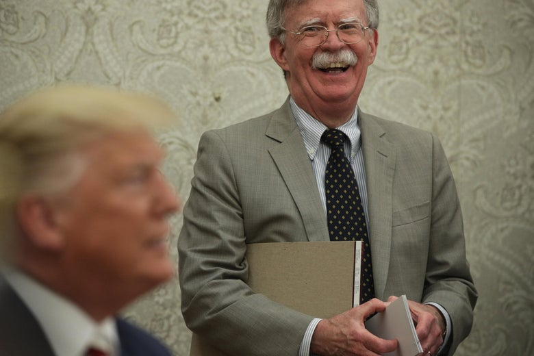 President Donald Trump speaks to members of the media as John Bolton listens at the Oval Office of the White House on August 20, 2019 in Washington, D.C.