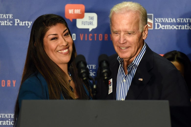 Lucy Flores and Joe Biden stand in front of a lectern and speak into microphones