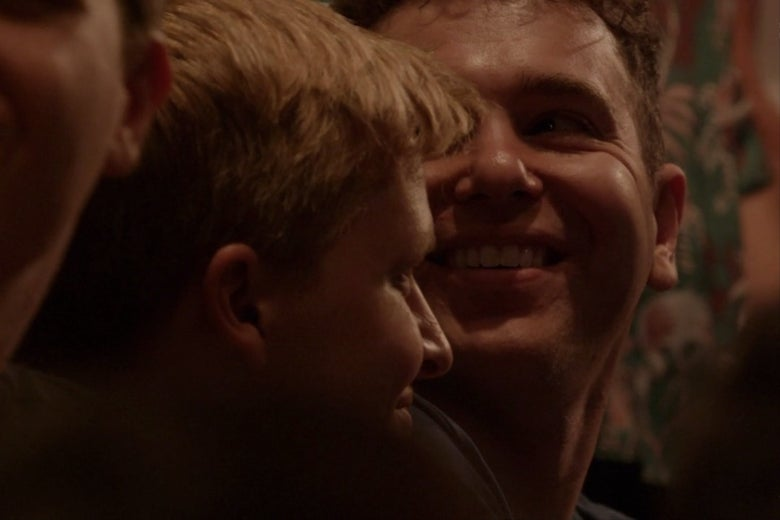 Ronan Farrow and Jon Lovett, sitting in a theater audience. Lovett is smiling widely.
