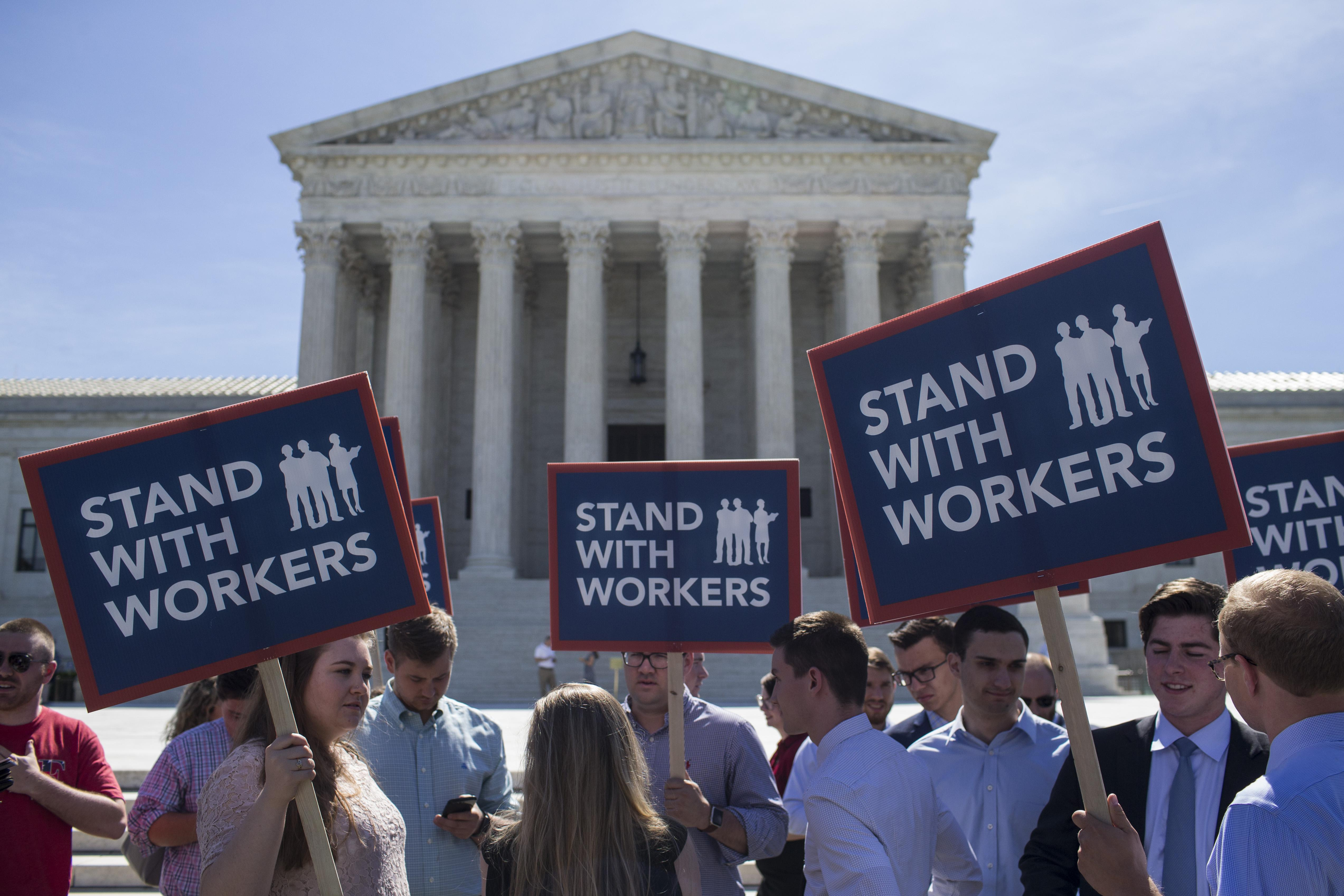 Demonstrators hold signs in front of the U.S. Supreme Court on June 25, 2018 in Washington, D.C.