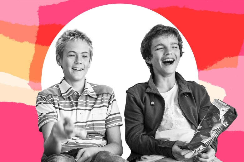 Two young boys laugh at a TV show.