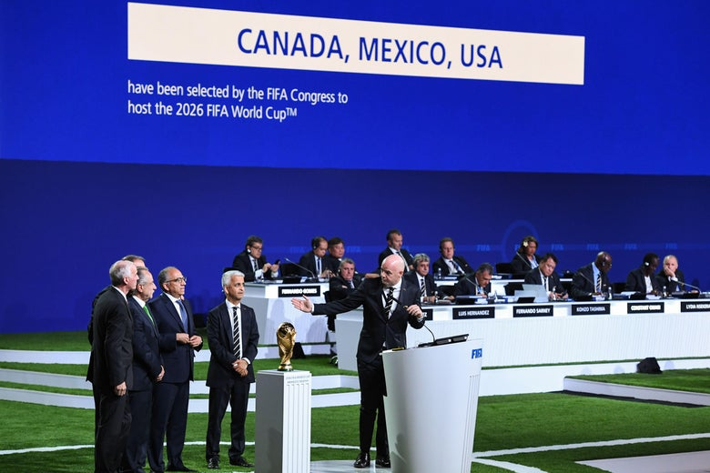 Men in suits stand to the side next to the World Cup trophy while another man in a suit talks from a white podium and gestures toward them.
