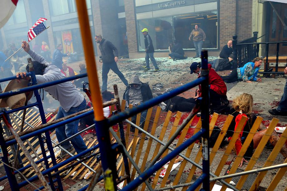 Destruction and injured people at the site of the one of the explosions that went off near the finish line of the 117th Boston Marathon.