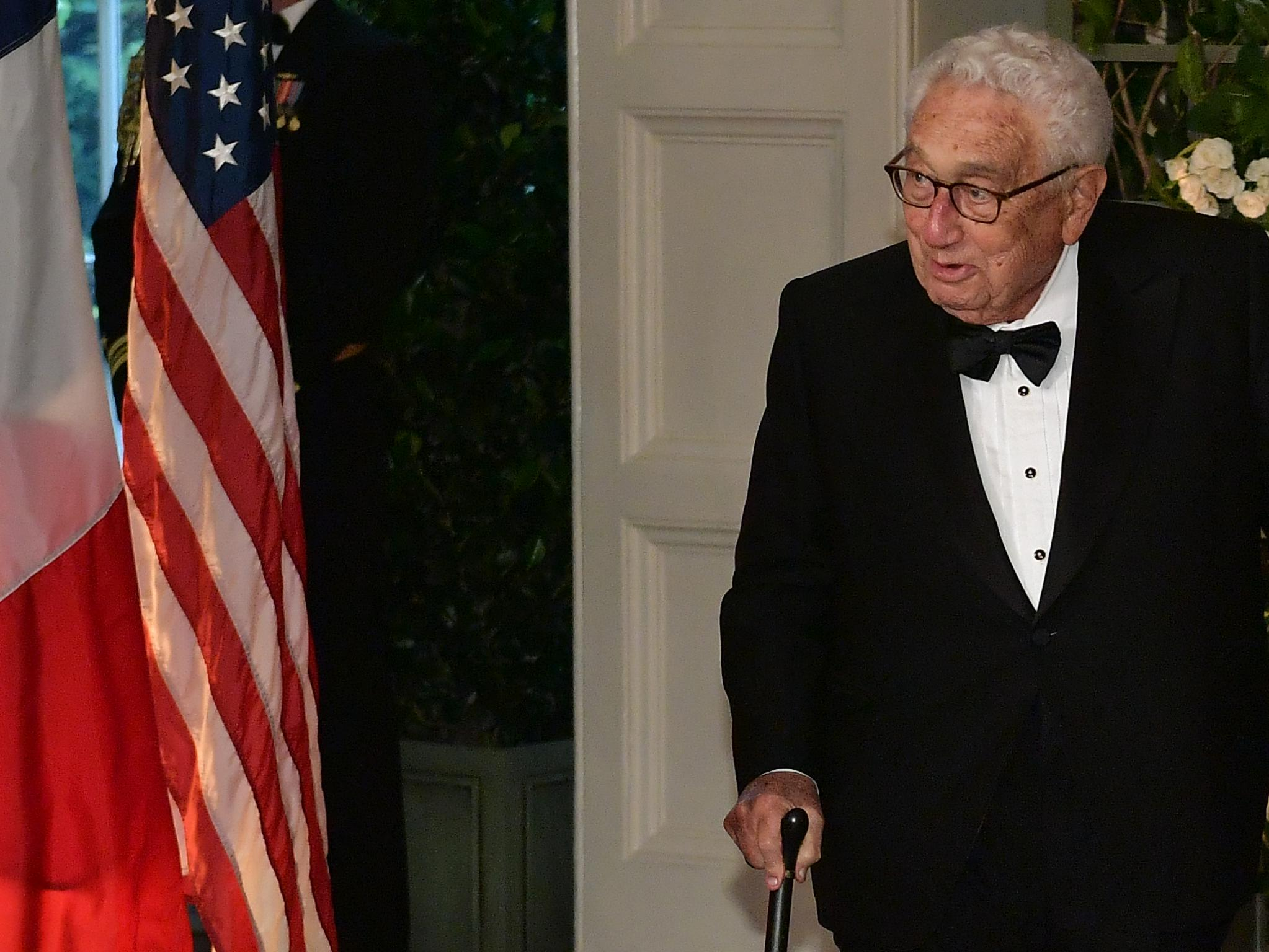 Henry Kissinger walking with a cane.