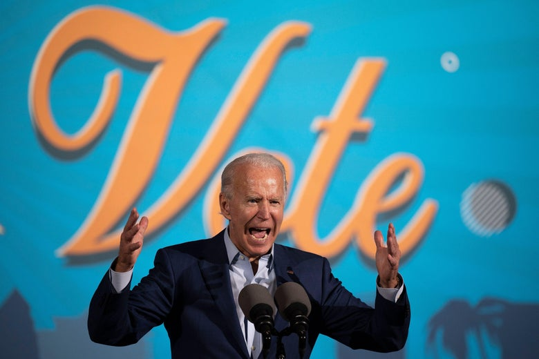 "Biden stands with his arms raised, shouting at a mic. The word ""vote"" is on a backdrop behind him."