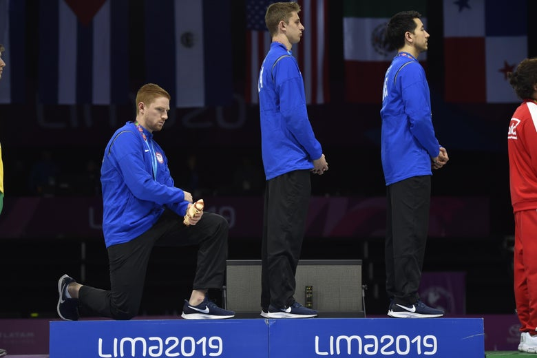 Race Imboden kneels next to Nick Itkin and Gerek Meinhardt on the medal stand.