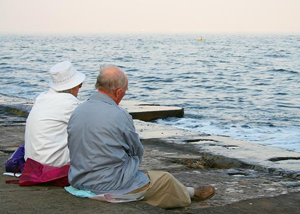 Older couple looking at the sea.