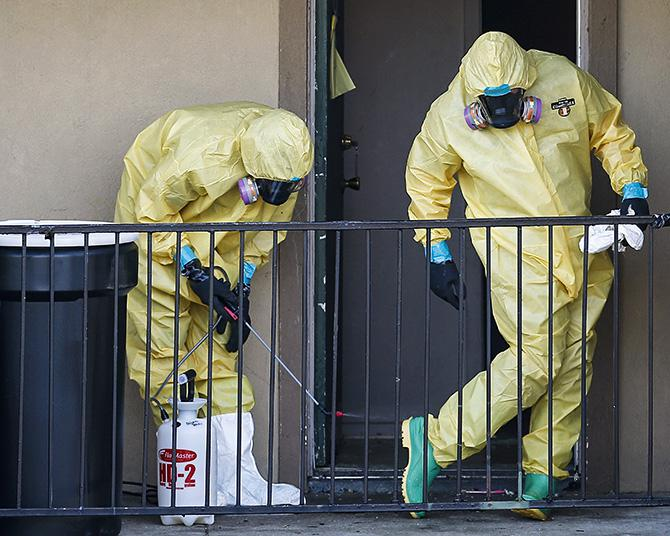 Workers in hazardous material suits clean up after removing the contents of the apartment unit where Thomas Eric Duncan, the first person to diagnosed with Ebola in the United States, was staying in Dallas, Texas, Oct. 6, 2014