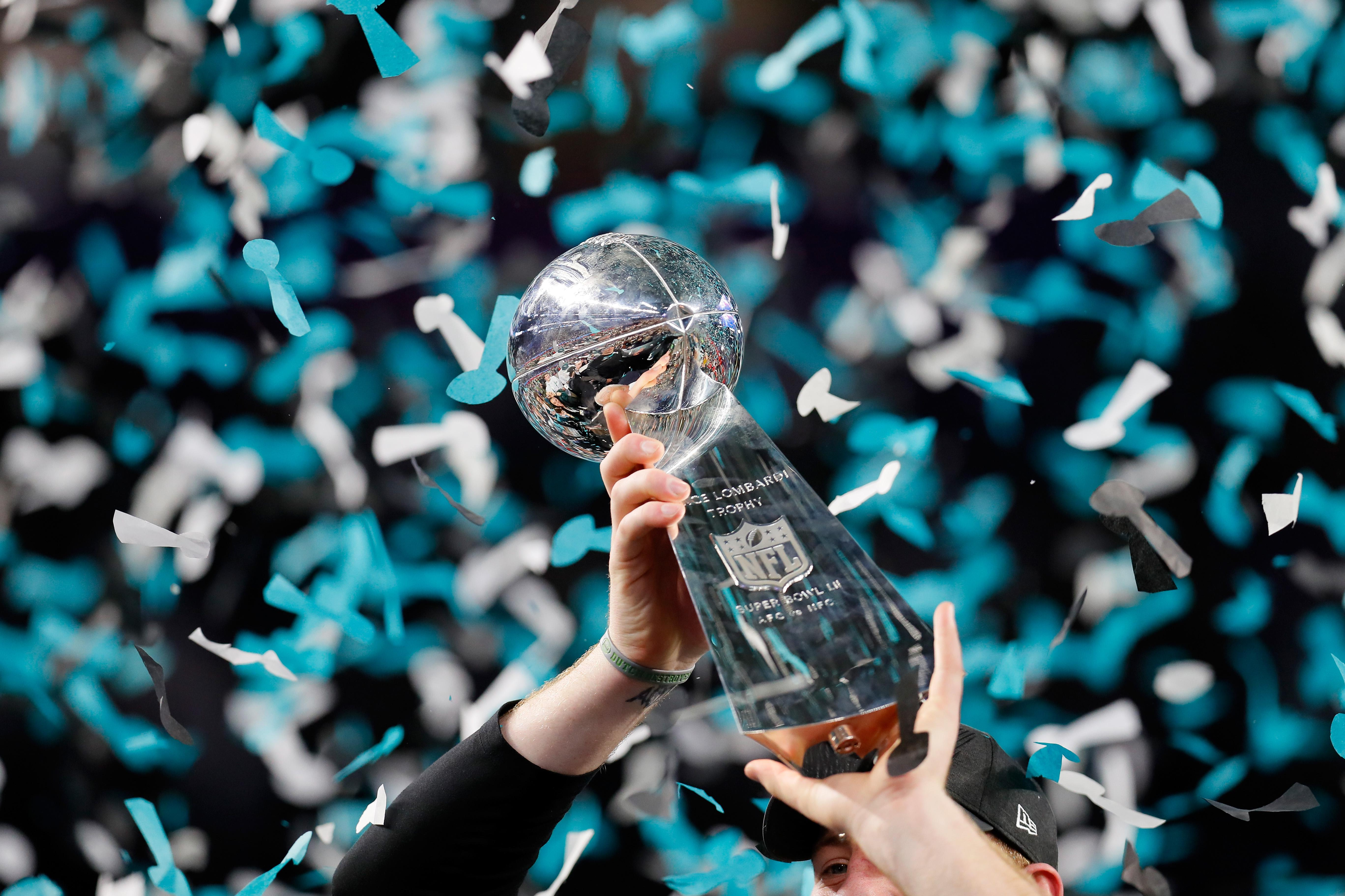 The Vince Lombardi Trophy is held in the air as confetti falls.