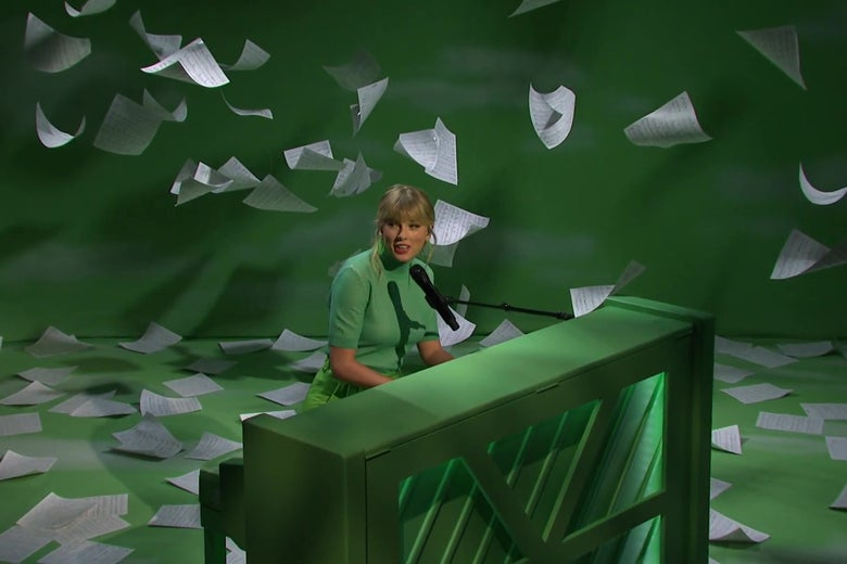 Taylor Swift plays a green piano on a green stage.