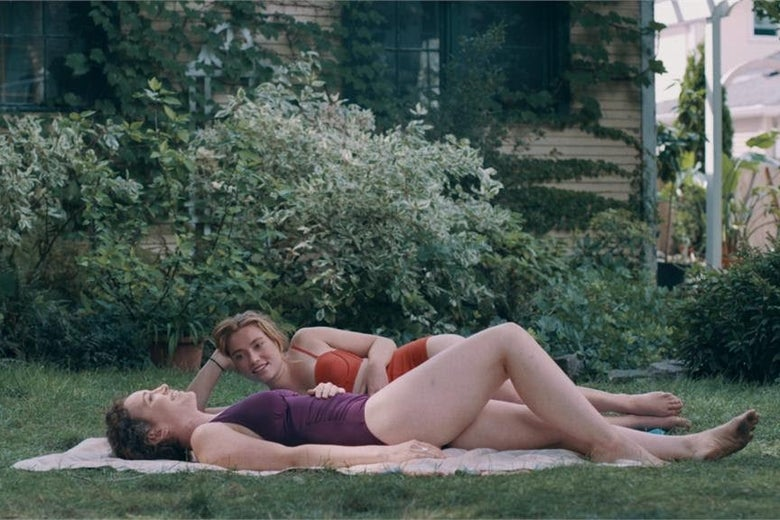 Jessie Pinnick and Rebecca Spence lounge on a blanket in the grass wearing bathing suits.