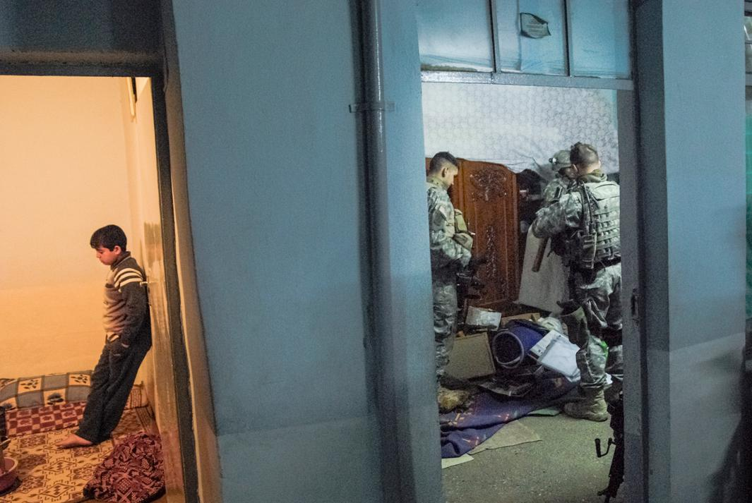 """American soldiers on a foot patrol noticed that two young men were eying them and fidgeting. Anticipating violence, they stormed their house. During the search the soldiers teased a young medic about his virginity. The soldiers had already searched hundreds of houses during their deployment, and the banter was casual as they swept the family's possessions onto the floor.In the next room they were questioning a boy. """"Have there been any new faces around the house lately?"""" """"Are your brothers coming and going at strange hours?"""" The boy muttered noncommittal answers and stared at the ground. They found no contraband in the house, but the hands of the young men came up with a faint residue of explosives. The lieutenant in charge of the platoon decided to detain them, though he thought they were innocent. The explosives tests were notoriously unreliable. They were blindfolded, and their hands bound with zip ties. The rest of the family began screaming and beating their chests. The soldiers locked them in a room and pushed the two stumbling men toward the Stryker.MOSUL. IRAQ. 2006"""