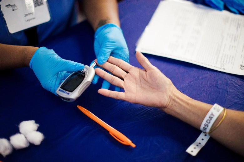 A patient's finger is poked for a diabetes test.
