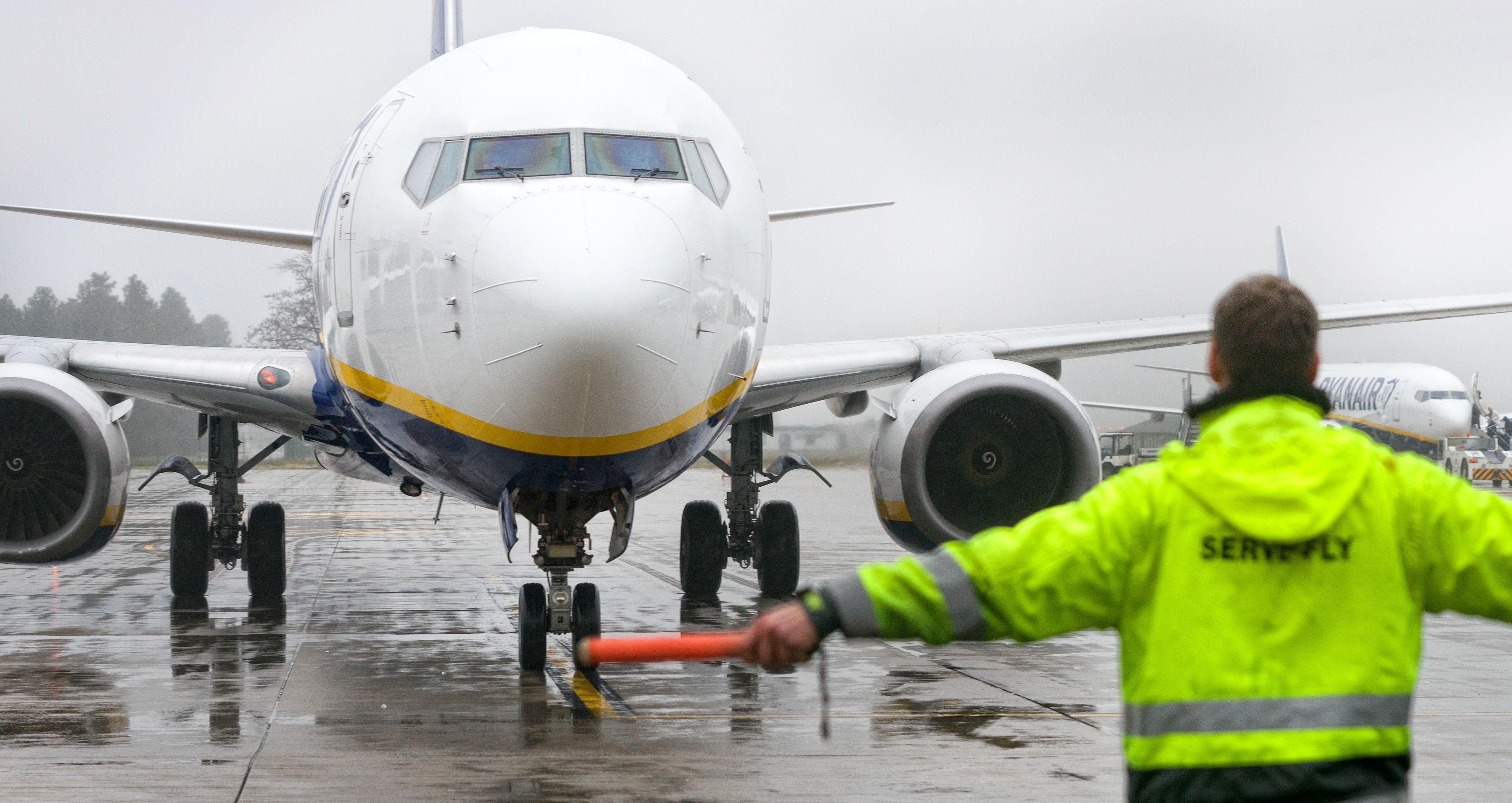An employee helps a passenger aircrafts of the Irish low-cost airline company Ryanair to park on the tarmac of the airport in Weeze, western Germany on December 22, 2017.         Passengers travelling with Ryanair in Germany on December 22, saw little disruption from a four-hour strike called by a pilots' union, with most flights leaving as scheduled, and only some delays. Germany's powerful Cockpit union had asked Ryanair pilots to walk off the job from 5-9am (0400-0800 GMT) in a battle for recognition from the Irish no-frills carrier whose workers have been calling for better pay and conditions across Europe. But the first-ever strike action by Ryanair pilots in the company's 32-year history appeared to have made little impact, with no cancellations reported.                   / AFP PHOTO / dpa / Arnulf Stoffel / Germany OUT        (Photo credit should read ARNULF STOFFEL/AFP/Getty Images)