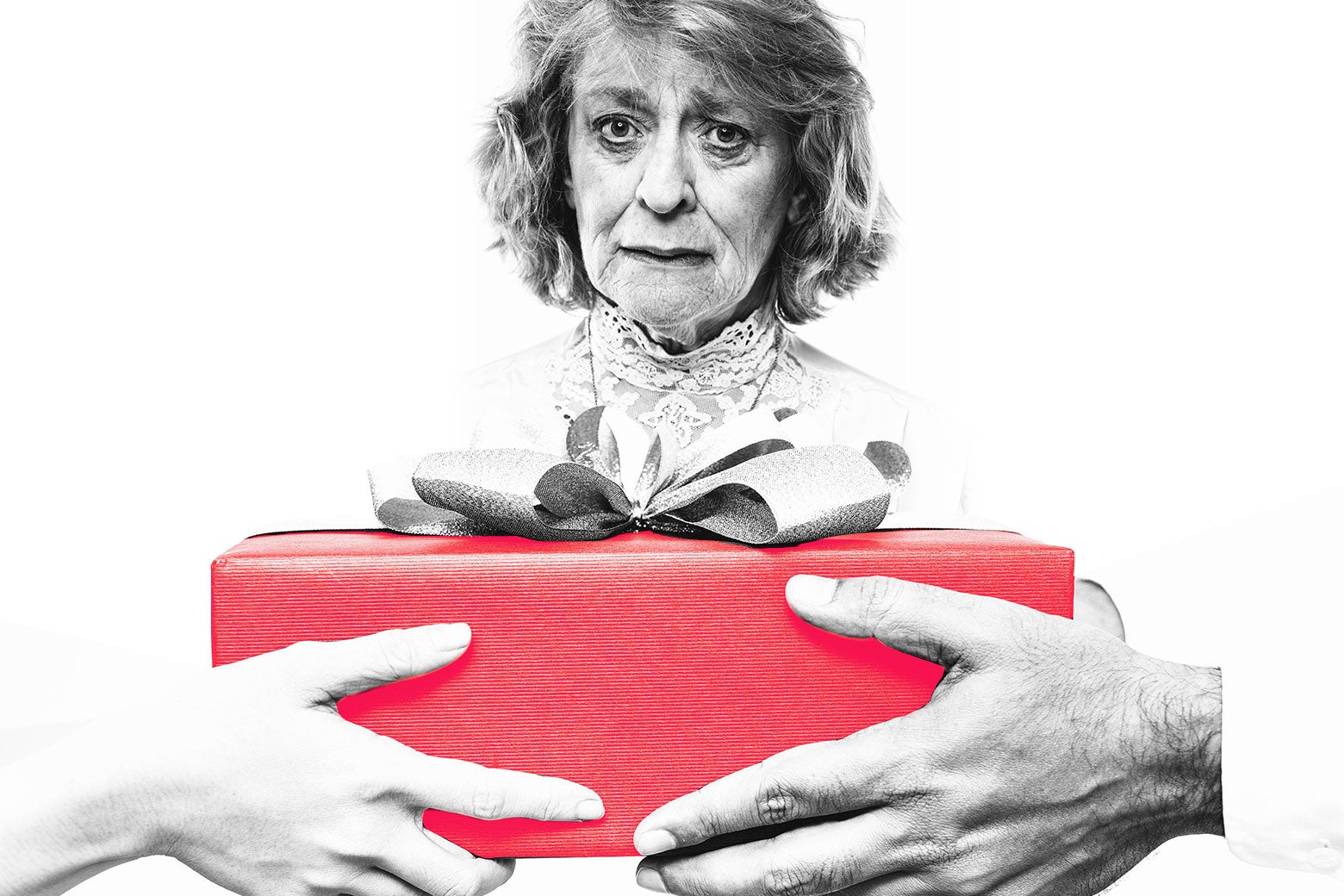 A sad looking older woman being presented with a gift held by two people.