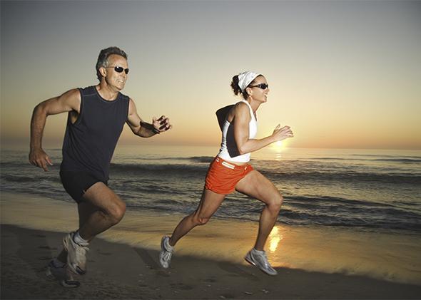 Couple running on beach at sunrise