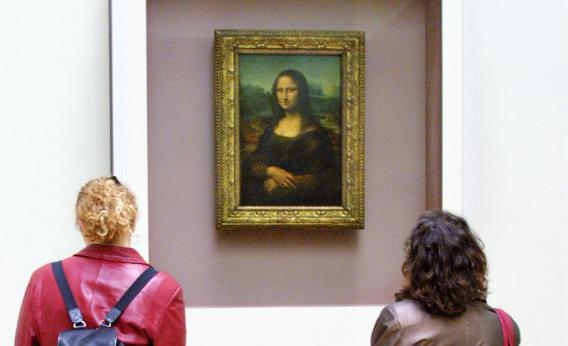 Visitors to the Louvre look at the Mona Lisa, which was stolen in 1911.