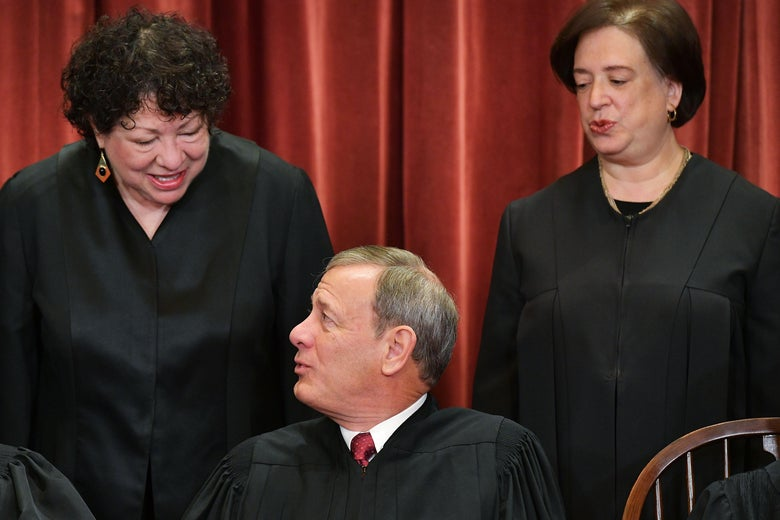 Associate Justice Sonia Sotomayor chats with Chief Justice John Roberts as Associate Justice Elena Kagan looks on while posing for the US Supreme Court official photo at the Supreme Court in Washington, D.C.