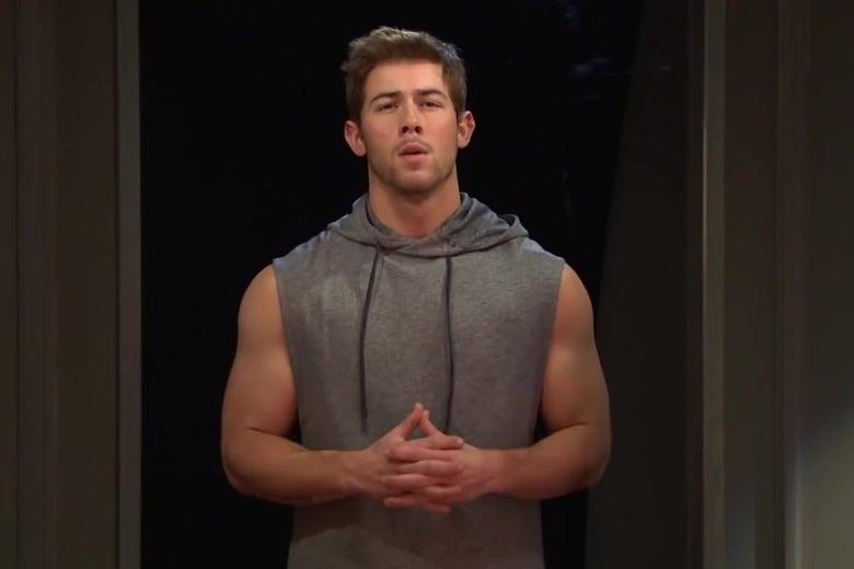 Nick Jonas, in a sleeveless hoodie, flexing.