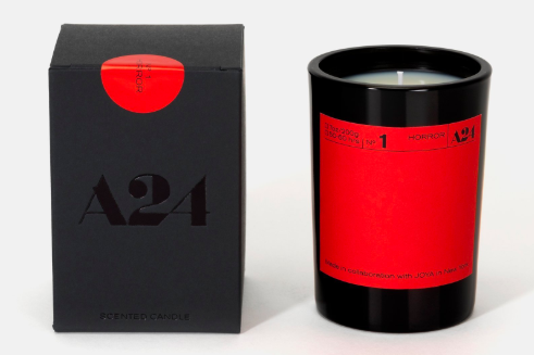 A red candle next to a black box.